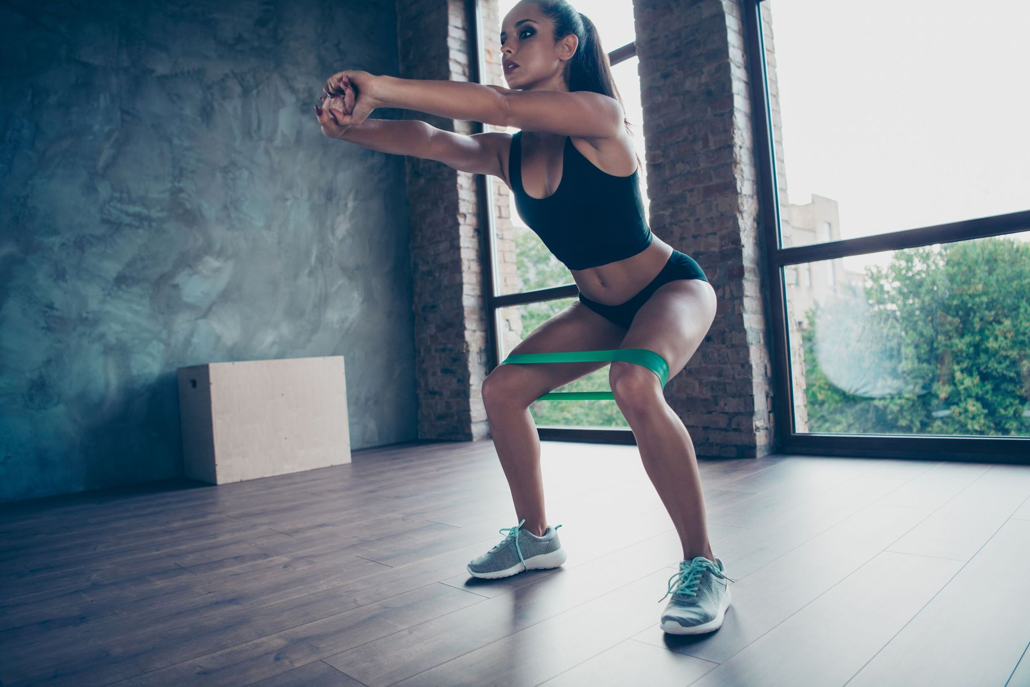 How to get a bigger butt: Woman doing resistance band squats